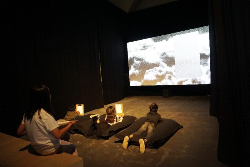 Vier Schüler:innen sind in einem abgedunkelten Raum und schauen einen Film auf einer Leinwand an.