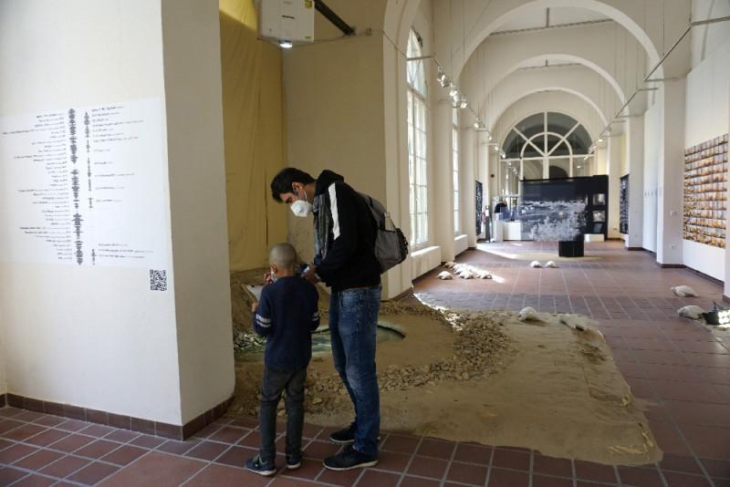 Ein Mann und ein Kind studieren ein Kunstwerk, das aus Sand und Wasser besteht.