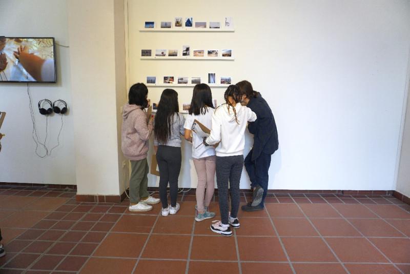 Vier Schüler:innen stehen vor einem Regal mit Fotografien, eine weibliche Person erzählt etwas dazu.
