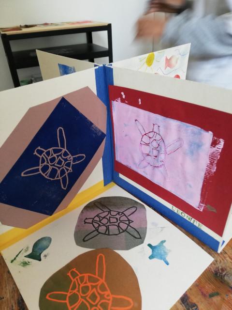 Ein Buch mit bunten Drucken von Schildkröten ist zu sehen, es ist aufegklappt auf einem Tisch und sieht von oben aus wie ein Kreuz mit verschiedenen Seiten.