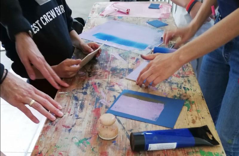 Sechs Hände auf einer Werkbank, sie halten Druckvorlagen und färben sie blau und rosa ein.