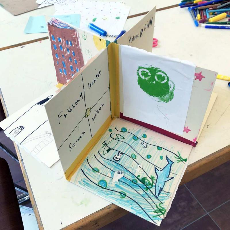3 D Buch, aufgeklappt, das bunt bedruckt und beklebt ist